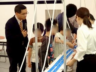 橋の科学館講演会「橋の仕組みと構造を模型で学ぼう」の写真:吊橋の模型にプラレールを走らせる様子