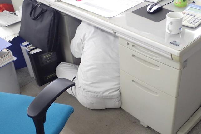 机の下に隠れて、落下物から身を守っています。